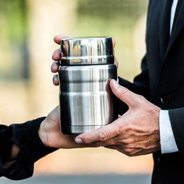A Man Holding An Urn