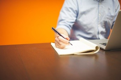 A Man Writing An Obituary