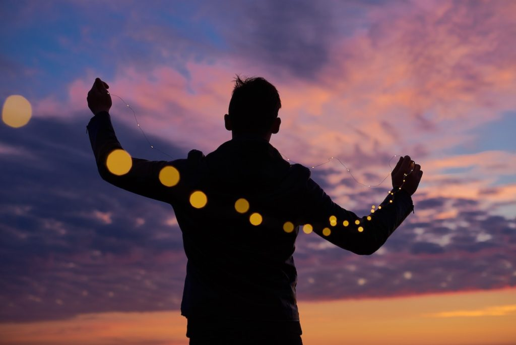 Man Holding A String Of Lights